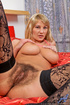 Busty blonde MILF in a bodysuit masturbating on a huge red bed