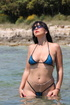Bikini-wearing brunette with ugly sunglasses shows her body on a beach