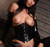 Black latex corset and stockings brunette posing half-naked on the stairs