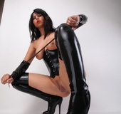 Black latex get-up brunette domme whipping herself on the floor