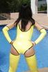 Bright yellow latex bodysuit brunette in shades posing poolside