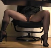 High heeled chick in black suit pulls down black pantyhose and touching