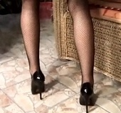 High heeled redhead in black stockings and undies rubbing her shaved pussy