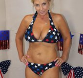 Patriotic blonde whore wearing red, white, and blue star bikini sits on