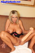 Nasty blonde milf sits on the brown couch near the hung artwork wearing
