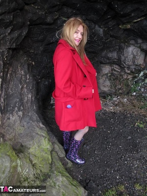 Mature brunette in fishnet stockings and rubber boots opens her red coat and showing her huge tits outdoors - XXXonXXX - Pic 8