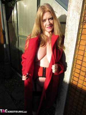 Mature brunette in fishnet stockings and rubber boots opens her red coat and showing her huge tits outdoors - XXXonXXX - Pic 9