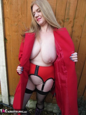 Mature brunette in fishnet stockings and rubber boots opens her red coat and showing her huge tits outdoors - XXXonXXX - Pic 13