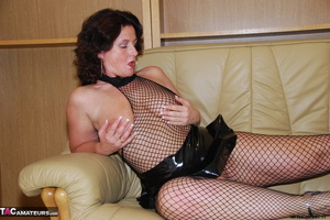 Busty brunette in fishnet bodystockings and high heels took off leather miniskirt and showing her shaved fuck holes - XXXonXXX - Pic 2