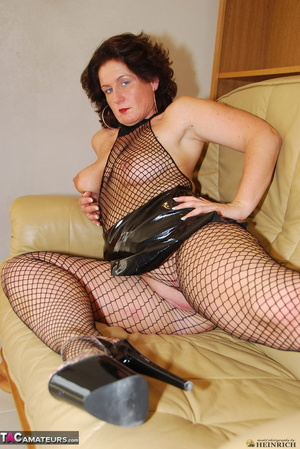 Busty brunette in fishnet bodystockings and high heels took off leather miniskirt and showing her shaved fuck holes - XXXonXXX - Pic 3