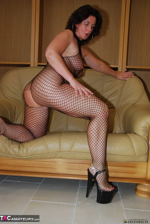 Busty brunette in fishnet bodystockings and high heels took off leather miniskirt and showing her shaved fuck holes - XXXonXXX - Pic 18