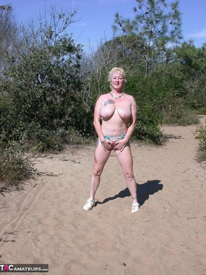 Mature blonde in white top and jeans miniskirt peeing outdoors before exposing her huge breast on the beach - XXXonXXX - Pic 9