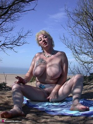 Mature blonde in white top and jeans miniskirt peeing outdoors before exposing her huge breast on the beach - XXXonXXX - Pic 11