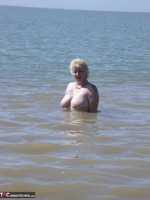 Mature blonde in white top and jeans miniskirt peeing outdoors before exposing her huge breast on the beach - XXXonXXX - Pic 14