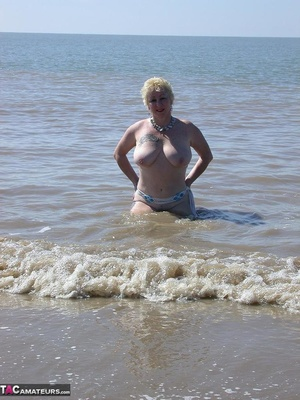Mature blonde in white top and jeans miniskirt peeing outdoors before exposing her huge breast on the beach - XXXonXXX - Pic 20