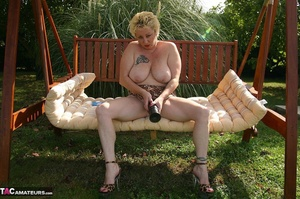 Big tits chick in sunglasses exposing her naked body and toying her pierced cunt with black dildo on the garden swing - XXXonXXX - Pic 14