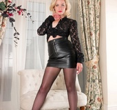 Short-haired blonde in leather miniskirt slowly undresses