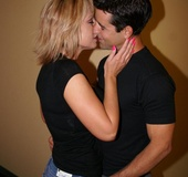 Kinky short haired blonde wearing black top and denim skirt kisses masculine