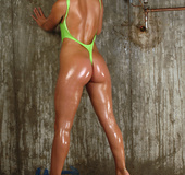Blue eyed brunette with oiled up booty posing in wet green bodysuit by