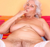 Horny granny gets her dirty twat wet while masturbating on couch.