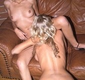 Blonde angel with huge fake tits lays on the brown leather sofa while